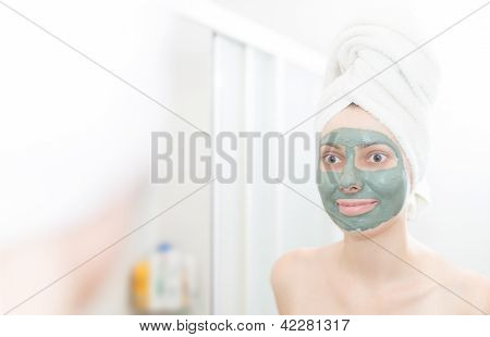 Woman with clay facial mask looking in mirror.