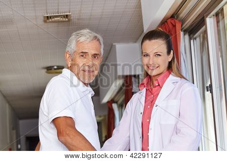 Senior man with nurse in floor of a hospital
