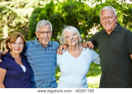 Four happy semiling senior people standing in nature in summer