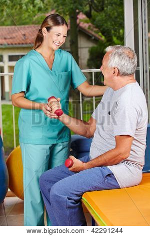 Senior man with dumbbells at physiotherapy with physiotherapist