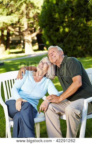 Old senior couple sitting in their garden and looking up