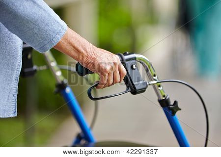 Hands of a senior woman on the handles of a walker