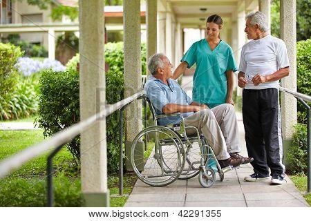Dos ancianos hablar con una enfermera en un jardín de hospital