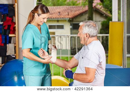 Nurse changing bandage on wrist of senior man at physiotherapy