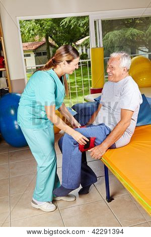 Elderly man moving his legs at physiotherapy with the help of physiotherapist