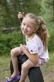 stock photo of tire swing  - Child swinging on tire - JPG