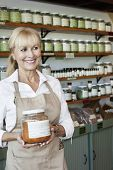 Happy senior salesperson with jar looking away in spice store