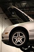 foto of car repair shop  - Car on lift in dim lite garage - JPG