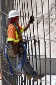 stock photo of road construction  - construction worker climbing grid of rebar on a road construction project - JPG