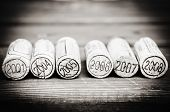 stock photo of bordeaux  - Dated wine bottle corks on the wooden background - JPG
