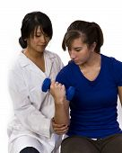 foto of physical therapist  - physical therapist helps a patient with light weights - JPG