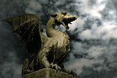 picture of stone sculpture  - Dragon on the stone over dramatic sky. Symbol of Ljubljana