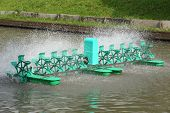 image of aerator  - Water treatment by paddle wheel aerator in pond - JPG