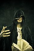 foto of warlock  - Young miserable man in hood with book - JPG