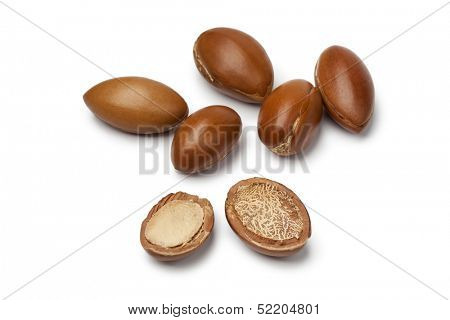 Whole and half Moroccan Argan nuts on white background