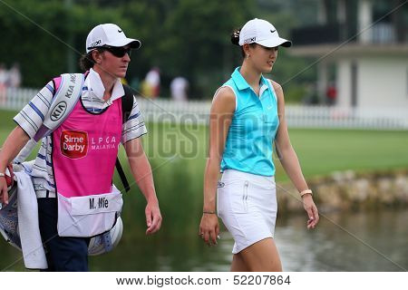 KUALA LUMPUR - OCTOBER 12: Michele Wie of USA walks with her caddy to the Hole 3 fairway of KLGCC course on Day 3 of the Sime Darby LPGA on October 12, 2013 in Kuala Lumpur, Malaysia.