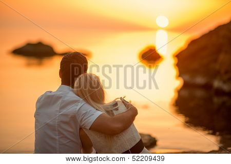 couple sitting on the beach at sunrise