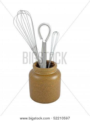 Three Metal Whisks In A Brown Ceramic Jar