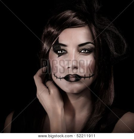 Closeup portrait of young woman with scary makeup isolated on black background, carnival costume of witch, Halloween party concept
