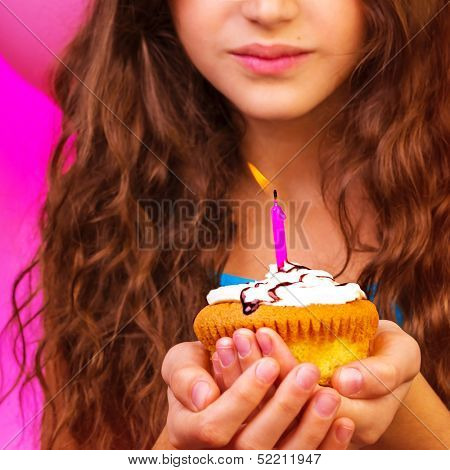 Lovely birthday girl make a wish with sweet festive cupcake in hands, enjoying holiday celebration, having fun indoors, happiness concept