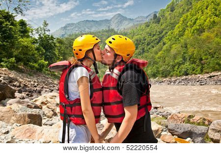 Man and woman kissing for good lack before a rafting on river in Nepal.