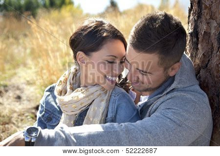 Outdoor close-up photo of young couple seated in grassy field.