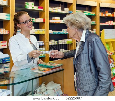 Pharmacist Serving A Senior Lady