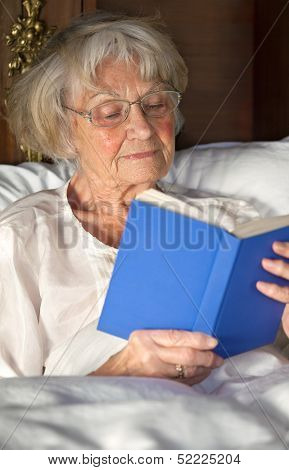 Elderly Pensioner Reading A Book In Bed