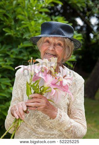 Happy Elderly Lady With Fresh Lilies