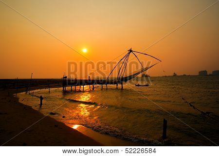Kochi Chinese Fishnets And The Boat With Fishermen On Sunset  In Kerala. Fort Kochin.
