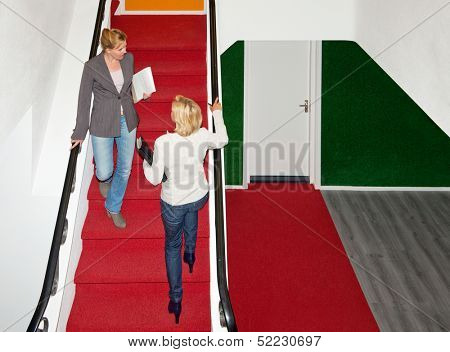 Two business women meeting eachother on a red carpeted stair case in a modern office building
