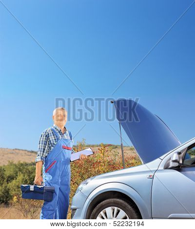 Mechanic standing near a broken car with open hood, on a road, shot with a tilt and shift lens