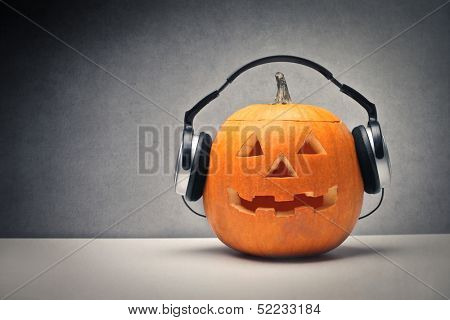 Halloween pumpkin with headphones for music