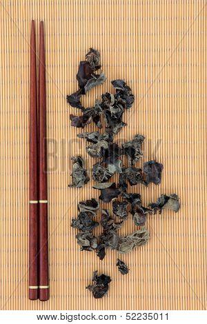 Black chinese mushroom fungus  with chopsticks over bamboo. Yun er.