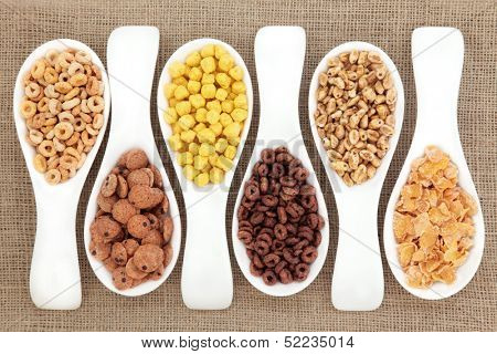 Breakfast cereal selection in white porcelain scoops over hessian background.