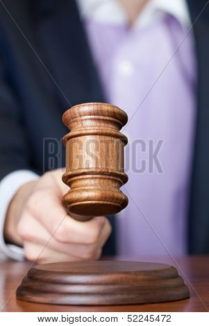 Man holding wooden gavel in the hand