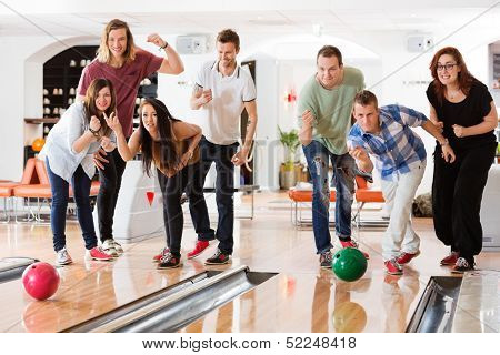 Young friends bowling while people cheering in club