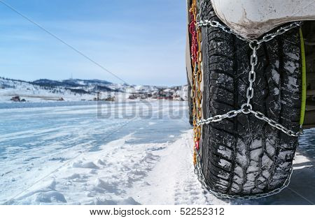 wheel of a car with chains on snow