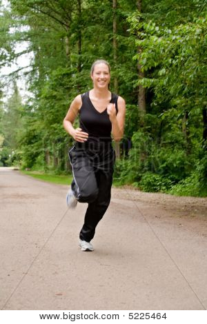 Sportive Young Woman Running Over A Forrest Road