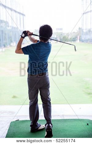 Young male golfer practicing his drive