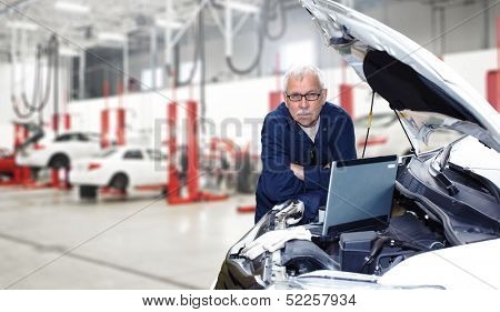 Car mechanic checking engine. Auto repair service.