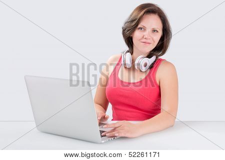 Young Woman Is Sitting In Front Of Laptop With Bluetooth Headphones
