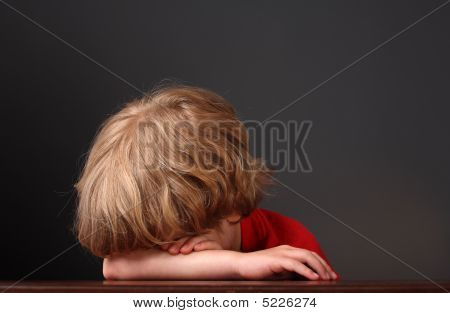 Young Boy Laying His Head On His Arms