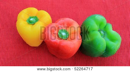 Three sweet peppers on red