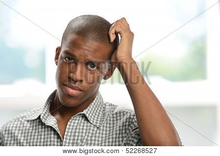 Worried black young man with hand on his head inside a building
