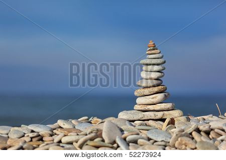 Stack of zen stones on pebble beach against blue water and sky background