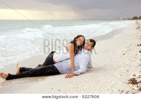 Woman Laying On Top Of Man At Beach Looking At Viewer