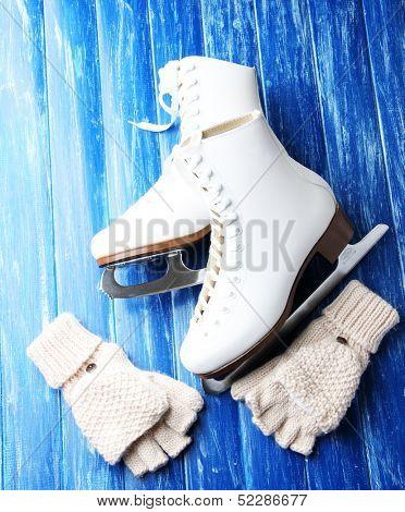 Wool fingerless gloves and skates for figure skating, on wooden background