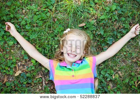 Little Funny Girl With Closed Eye Lying On Grass