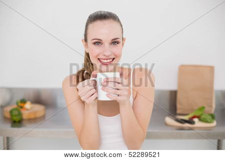 Happy young woman holding mug in the kitchen at home